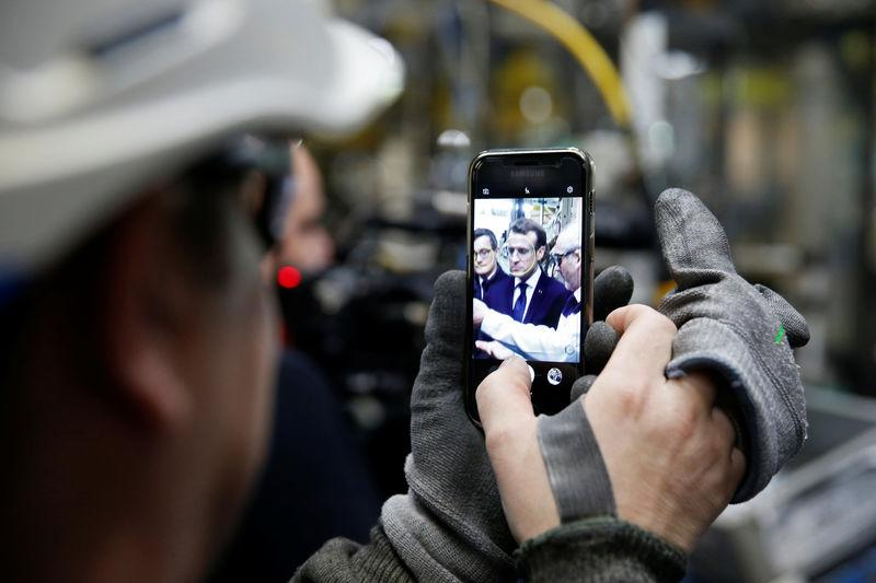 An employee uses a mobile phone to make of picture of French President Emmanuel Macron as he visits Toyota's automobile manufacturing plant in Onnaing, France, January 22, 2018. REUTERS/Pascal Rossignol