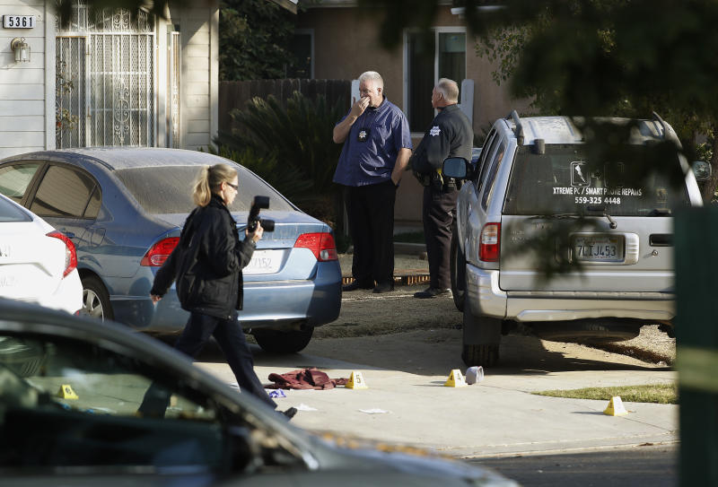 Fresno police Investigator Brooke Passmore, left, works on the driveway on Lamona Ave. where a shooting took place at a house party which involved multiple fatalities and injuries in Fresno, Calif., Monday, Nov. 18, 2019. (AP Photo/Gary Kazanjian)