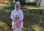 Ten-year-old Cameron Fox and her 4-year-old sister, Lexi, of Brookfield, Ill., are dressed as unicorns for Halloween with plastic face shields to protect against COVID-19, as they visit the home of family friends in nearby River Forest, Ill., on Saturday, Oct. 31, 2020. Their grandmother bought the shields as their mother, Julie, is taking them to visit the homes of friends and family in the area, in pace of the traditional trick-or-treating. (AP Photo/Don Babwin)