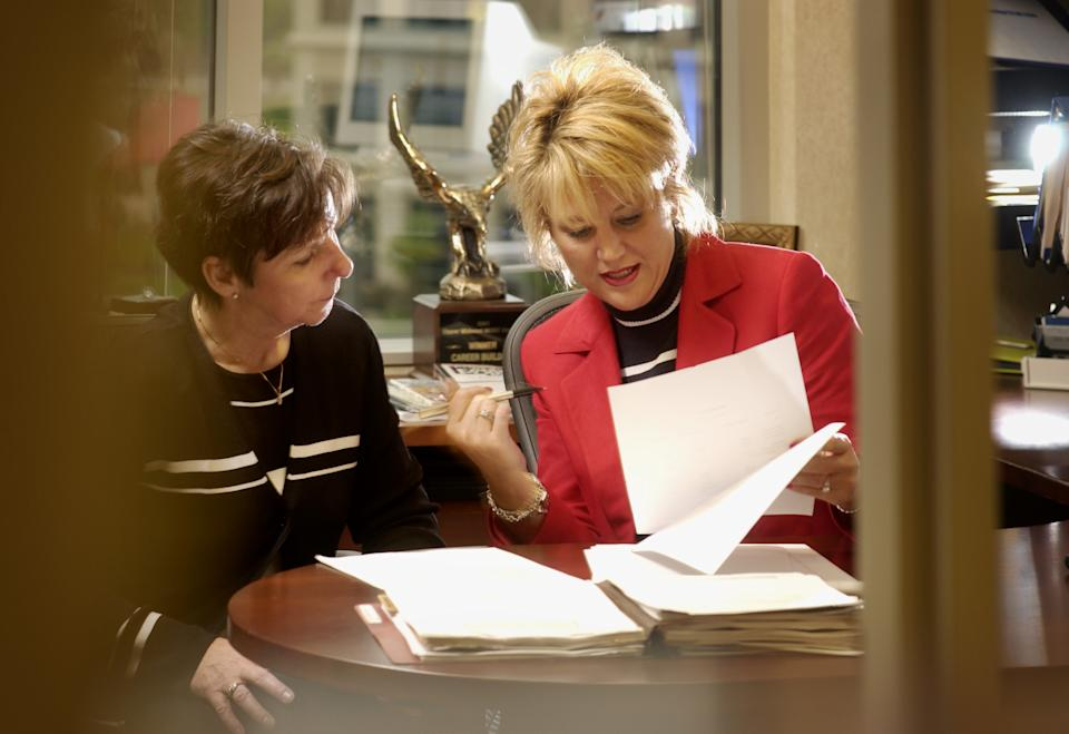 MONDAY_06/03/02_Edina - - - - -  Financial Planner Melissa Held-Soderberg (right-in red) works with client Linda Adam-Mellang (left-in black) at Held-Soderberg's Edina office.(Photo By DAVID BREWSTER/Star Tribune via Getty Images)