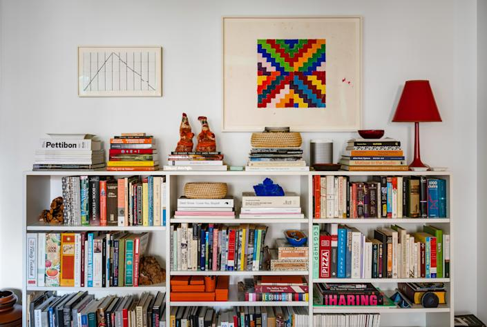 "<div class=""caption""> A jam-packed bookshelf is topped by an equally colorful artwork. </div>"