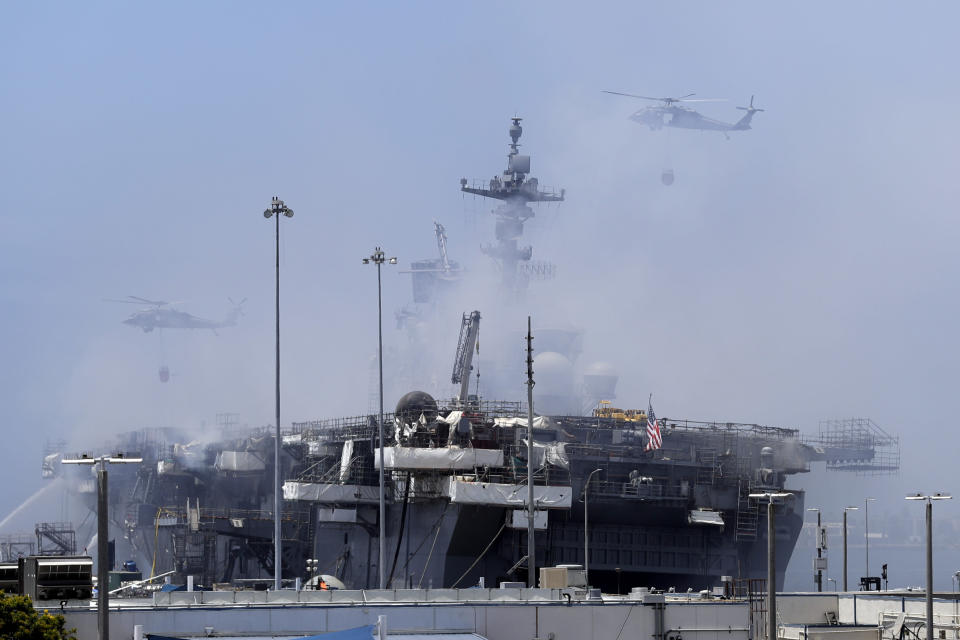Helicopters approach the USS Bonhomme Richard as crews fight the fire Monday, July 13, 2020, in San Diego. Fire crews continue to battle the blaze Monday after 21 people suffered minor injuries in an explosion and fire Sunday on board the USS Bonhomme Richard at Naval Base San Diego. (AP Photo/Gregory Bull)