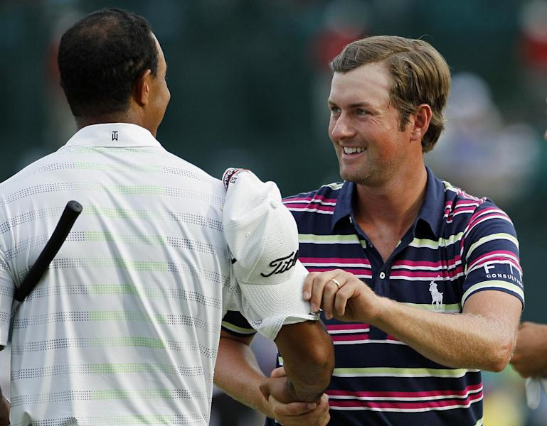 Webb Simpson, right, shakes hand with Tiger Woods on the 18th green following their first round of the Wells Fargo Championship golf tournament at Quail Hollow Club in Charlotte, N.C., Thursday, May 3, 2012. (AP Photo/Gerry Broome)