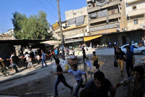 Syrians run for cover as a helicopter hovers over the northern city of Aleppo