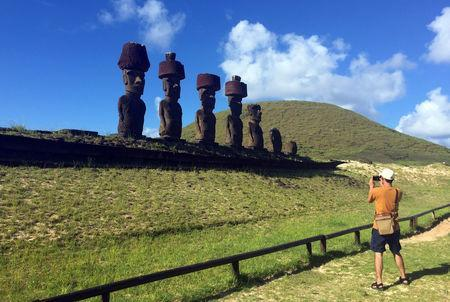 """A tourist take a picture of statues named """"Moai"""" at Easter Island, Chile February 12, 2019. REUTERS/Marion Giraldo/Files"""