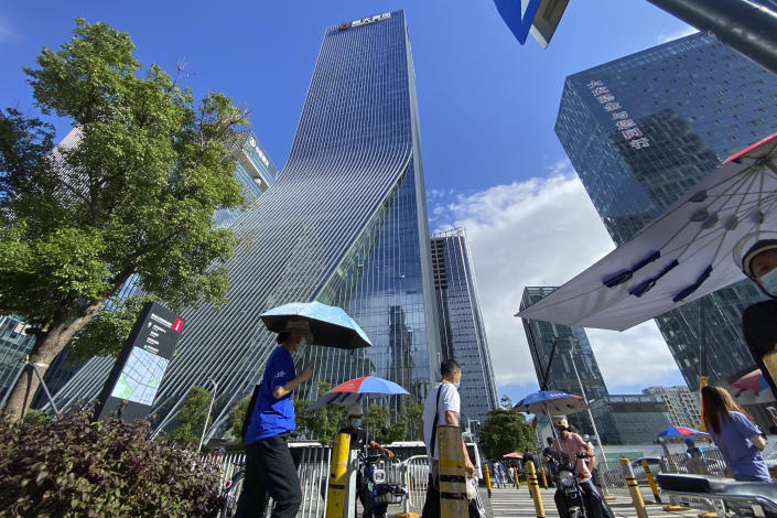 Residents pass near the headquarters for Evergrande in Shenzhen in southern China, Thursday, Sept. 23, 2021. The Chinese real estate developer whose struggle to avoid defaulting on billions of dollars of debt has rattled global markets says it will pay interest due Thursday to bondholders in China but gave no sign of plans to pay on a separate bond abroad. (AP Photo/Ng Han Guan)