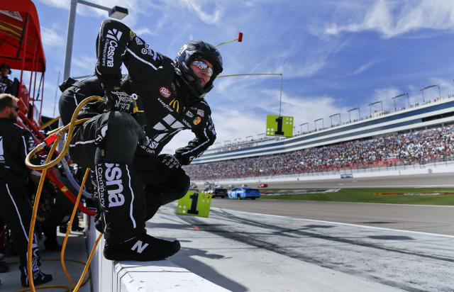 A pit crew member prepares for Travis Kvapil to make a pit stop during a NASCAR Sprint Cup Series auto race, Sunday, March 9, 2014, in Las Vegas. (AP Photo/Julie Jacobson)