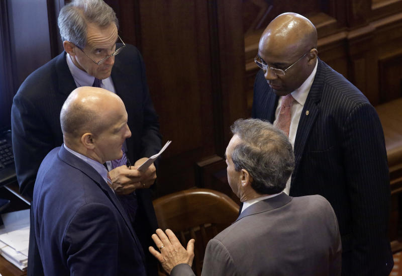 In this Thursday, May 30, 2013 photo, Illinois Senate President John Cullerton, D-Chicago, bottom, speaks with Illinois Sen. Kwame Raoul, D-Chicago, right, Illinois Sen. Dan Kotowski , D-Park Ridge, left, and a legislative staffer, top, while on the Senate floor during session at the Illinois State Capitol in Springfield, Ill. Illinois lawmakers scramble to finish up business in their spring session with votes to legalize gay marriage, pension reform, gun legislation. (AP Photo/Seth Perlman)
