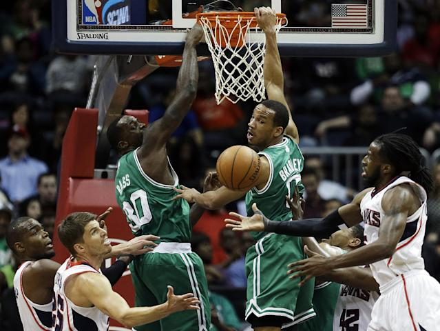 Boston Celtics' Brandon Bass and Avery Bradley, center left and right, watch a rebound fall into the hands of Atlanta Hawks' DeMarre Carroll, right, as teammates Paul Millsap, left, and Kyle Korver look on in the second quarter of an NBA basketball game, Wednesday, April 9, 2014, in Atlanta. (AP Photo/David Goldman)