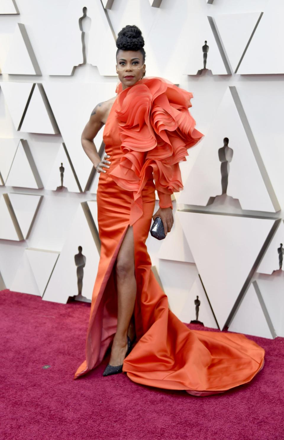 <p>Wearing a voluminous red one-shoulder gown.</p>