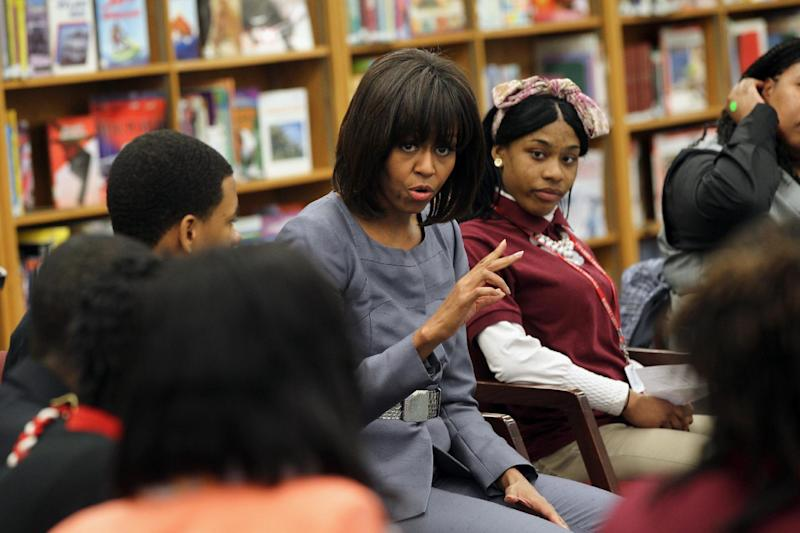 FILE - In this April 10, 2013 file-pool photo, first lady Michelle Obama talks to students at Harper High School in Chicago. By reaching beyond the pair of relatively safe issues she has pushed _ reducing childhood obesity and rallying public support for military families _ the Harvard-trained lawyer who some say has played it safe is showing a willingness to step outside of her comfort zone. (AP Photo/Nancy Stone, Pool)