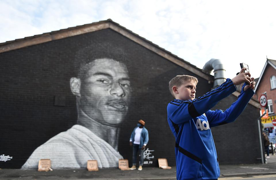 MANCHESTER, ENGLAND - NOVEMBER 07: A boy  takes a photo of a Mural of Manchester United footballer Marcus Rashford, created by local street artist Akse, after the footballer received an MBE for his work campaigning for the government to provide meals to impoverished children on November 07, 2020 in Manchester, England. (Photo by Nathan Stirk/Getty Images)