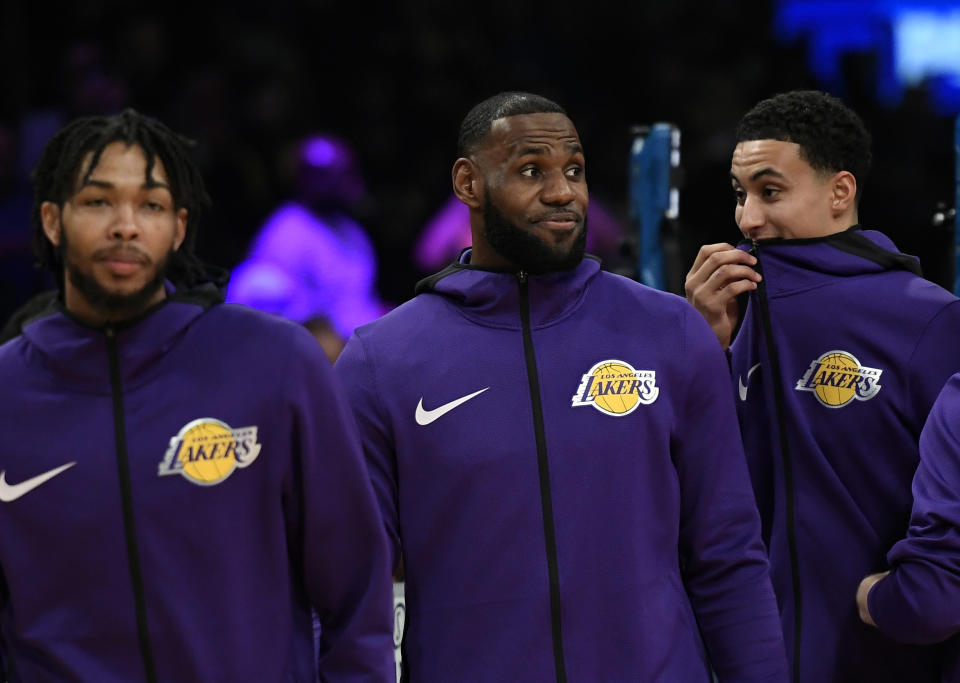 LeBron James, Brandon Ingram and Kyle Kuzma wear purple warmup hoodies before a game.