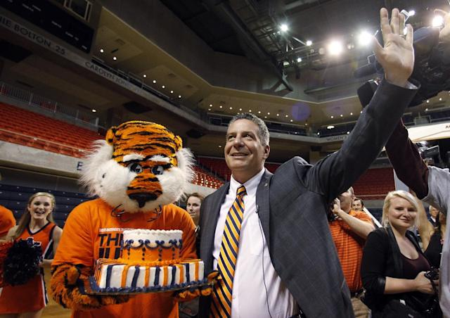 Auburn's new men's basketball coach, Bruce Pearl, waves to fans after he received a birthday cake from Auburn mascot Aubie on Tuesday, March 18, 2014, in Auburn, Ala. (AP Photo/Butch Dill)