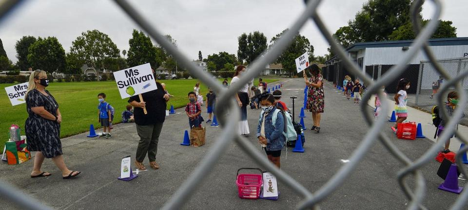 "<span class=""caption"">Teachers organize their socially distanced students at Weaver Elementary School in Rossmoor, California.</span> <span class=""attribution""><a class=""link rapid-noclick-resp"" href=""https://www.gettyimages.com/detail/news-photo/kindergarten-and-tk-teachers-organize-their-students-on-the-news-photo/1271437757"" rel=""nofollow noopener"" target=""_blank"" data-ylk=""slk:Jeff Gritchen/MediaNews Group/Orange County Register via Getty Images"">Jeff Gritchen/MediaNews Group/Orange County Register via Getty Images</a></span>"
