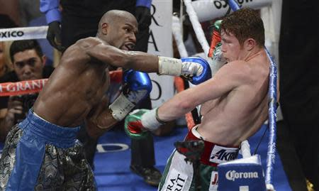 Floyd Mayweather Jr. (L) of the U.S. punches on WBC/WBA 154-pound champion Canelo Alvarez of Mexico during their title fight at the MGM Grand Garden Arena in Las Vegas, Nevada, September 14, 2013. REUTERS/Mark Hundley