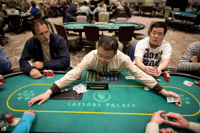 FILE - In this Feb. 27, 2013 file photo, dealer Han Kim, center, gathers up chips after a hand of Texas Hold 'em at a poker room in Caesar's Palace in Las Vegas.  Unlike the 2000s when casinos competed to lure fans of the game, poker's appeal has been weakening during this decade. Strip casinos had 405 tables and made $97 million in 2007. In contrast, the game only netted casinos $78 million last year after the number of tables decreased to 320.  (AP Photo/Julie Jacobson, File)