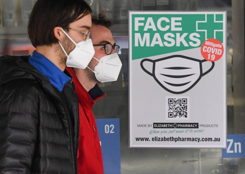 People wearing face masks walk past a sign advertising masks in Melbourne.