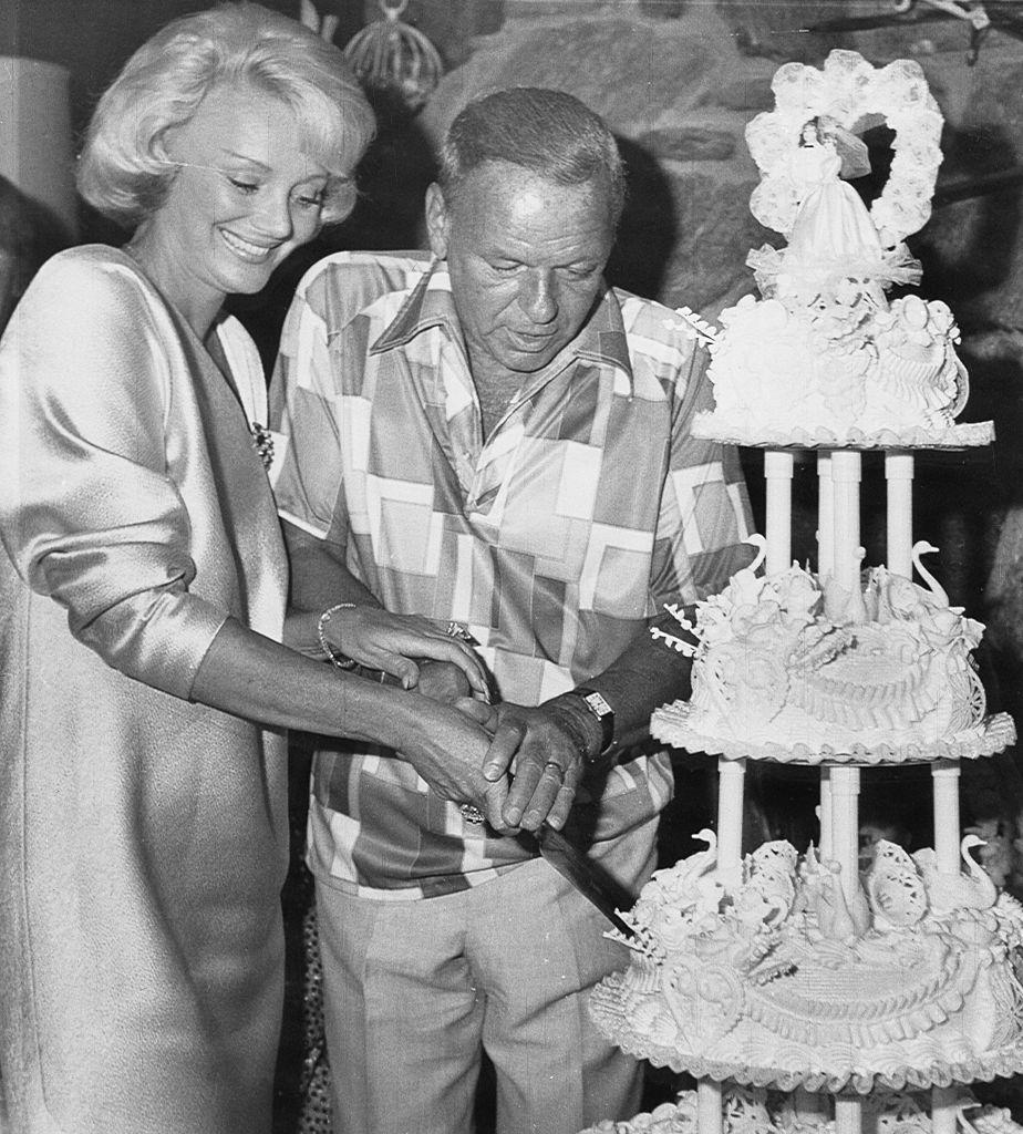 <p>Frank Sinatra and his new bride, Barbara Marx, cut into their wedding cake at the famous singer's Palm Springs ranch house in 1976.</p>