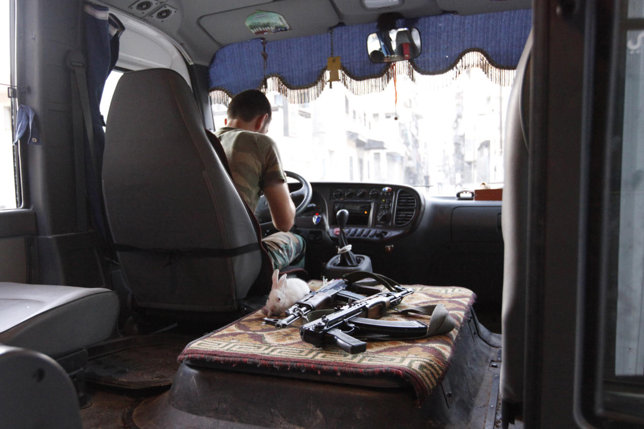 A rabbit is pictured next to weapons in a Free Syrian Army bus in Bustan Al-Basha district in Aleppo September 18, 2012. REUTERS/Zain Karam (SYRIA - Tags: CONFLICT CIVIL UNREST POLITICS ANIMALS)