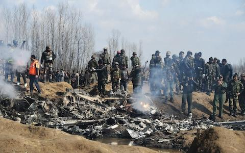 Indian soldiers and Kashmiri onlookers stand near the remains of an Indian Air Force helicopter after it crashed in Budgam district - Credit: Tauseef Mustafa/AFP
