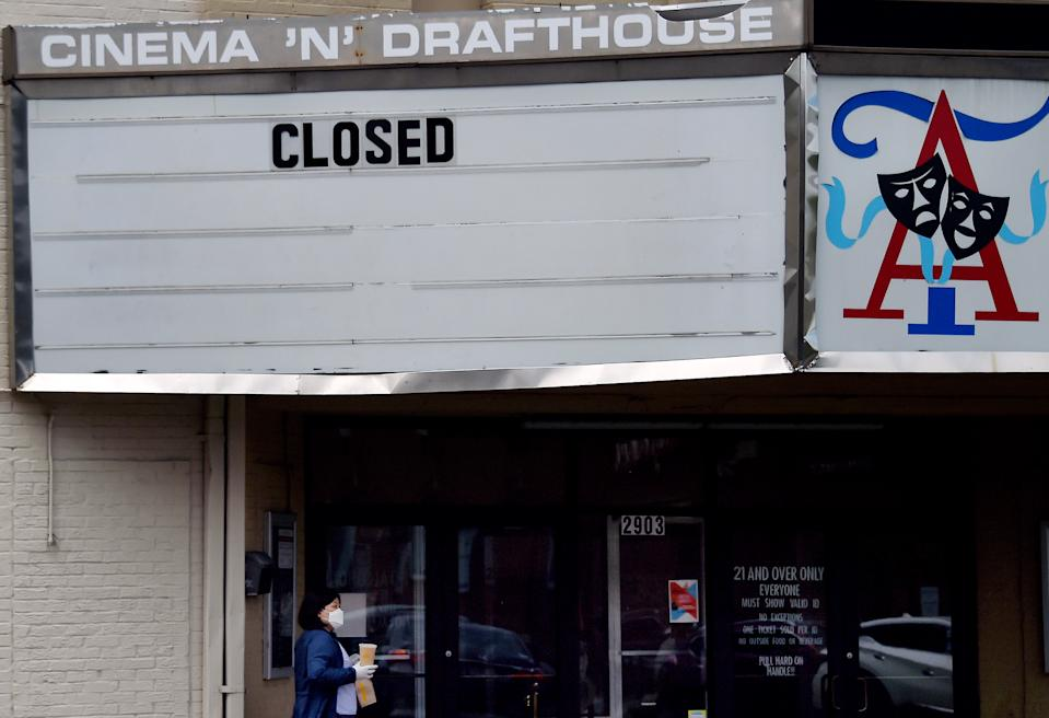 A woman wearing a face mask walks past the closed Arlington Cinema and Drafthouse movie theater amid the coronavirus pandemic on May 14, 2020 in Arlington, Virginia. - Another 3 million people filed initial unemployment claims last week on a seasonally adjusted basis, according to the Department of Labor. (Photo by Olivier DOULIERY / AFP) (Photo by OLIVIER DOULIERY/AFP via Getty Images)