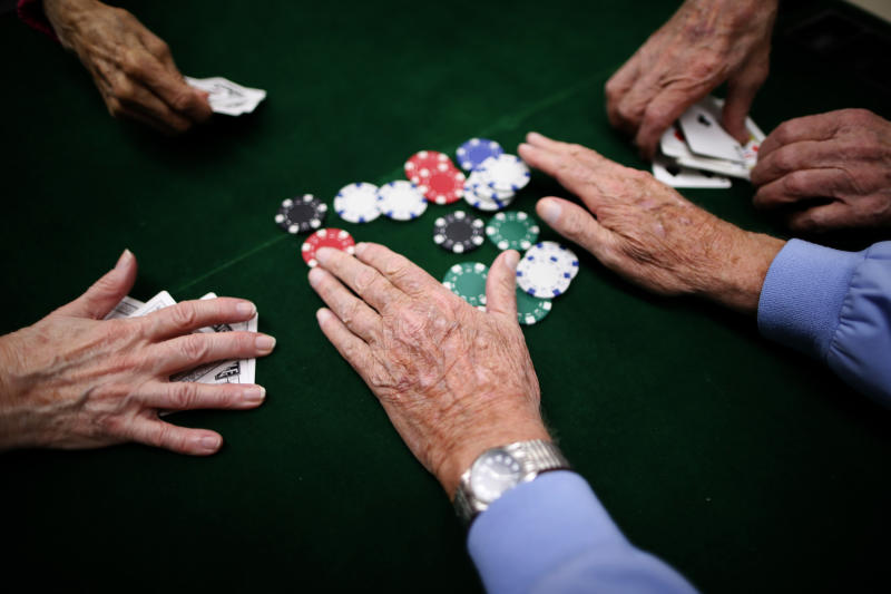 Retirees play poker at a singles club in Sun City, Arizona, January 4, 2013. Sun City was built in 1959 by entrepreneur Del Webb as America?s first active retirement community for the over-55's. Del Webb predicted that retirees would flock to a community where they were given more than just a house with a rocking chair in which to sit and wait to die. Today?s residents keep their minds and bodies active by socializing at over 120 clubs with activities such as square dancing, ceramics, roller skating, computers, cheerleading, racquetball and yoga. There are 38,500 residents in the community with an average age 72.4 years. Picture taken January 4, 2013. REUTERS/Lucy Nicholson (UNITED STATES - Tags: SOCIETY) ATTENTION EDITORS - PICTURE 8 OF 30 FOR PACKAGE 'THE SPORTY SENIORS OF SUN CITY' SEARCH 'SUN CITY' FOR ALL IMAGES