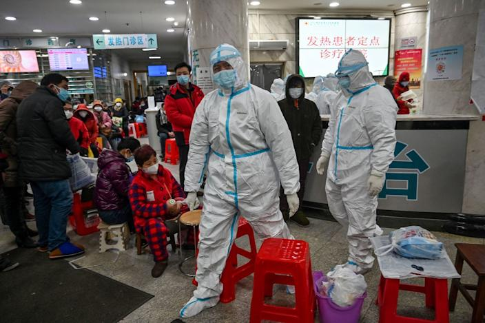 Medical staff members wearing protective clothing to help stop the spread of a deadly virus which began in the city, walk next to patients (L) waiting for medical attention at the Wuhan Red Cross Hospital in Wuhan on January 25, 2020.