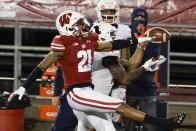 Illinois punter Blake Hayes catches a pass with Wisconsin cornerback Caesar Williams defending during the second half of an NCAA college football game Friday, Oct. 23, 2020, in Madison, Wis. Wisconsin won 45-7. (AP Photo/Morry Gash)