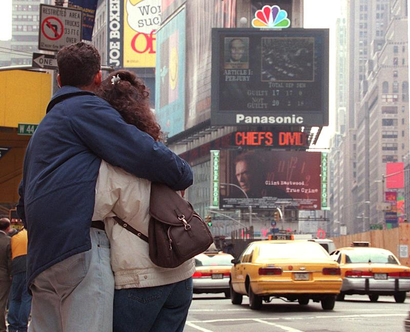 """A couple watches the NBC jumbotron in Times Square display the """"Not Guilty"""" verdict on the Obstruction of Justice charges against President Bill Clinton during his impeachment trial on Capitol Hill February 12, 1999. (Photo: Timothy A. Clary/AFP via Getty Images)"""