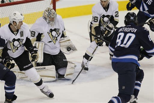 A stickless Pittsburgh Penguins' goaltender Marc-Andre Fleury (29) saves the shot from Winnipeg Jets' forward Nik Antropov (80) during first-period NHL hockey game action in Winnipeg, Manitoba, Friday, Dec. 23, 2011. (AP Photo/The Canadian Press, John Woods)