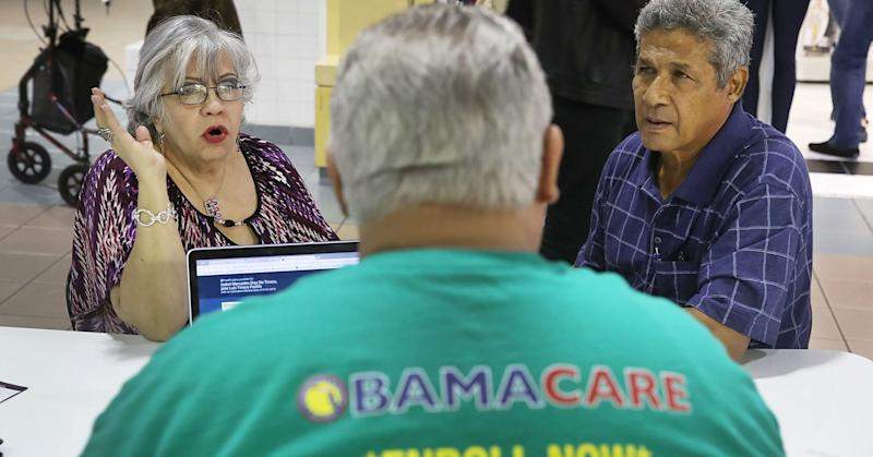Isabel Diaz Tinoco (L) and Jose Luis Tinoco speak with Otto Hernandez, an insurance agent from Sunshine Life and Health Advisors, as they shop for insurance under the Affordable Care Act at a store setup in the Mall of Americas on November 1, 2017 in Miami, Florida.