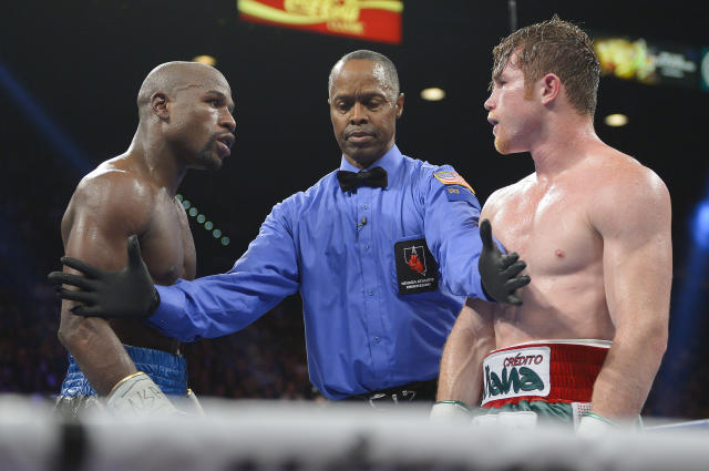 Referee Kenny Bayless, center, separates Floyd Mayweather Jr., left, and Canelo Alvarez at the end of the 11th round during a 152-pound title fight, Saturday, Sept. 14, 2013, in Las Vegas. (AP Photo/Mark J. Terrill)
