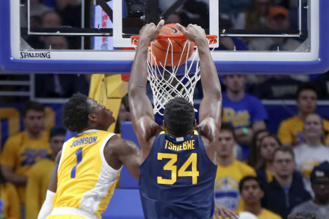 West Virginia's Oscar Tshiebwe (34) dunks as Pittsburgh's Xavier Johnson (1) defends during the first half of an NCAA college basketball game, Friday, Nov. 15, 2019, in Pittsburgh. (AP Photo/Keith Srakocic)