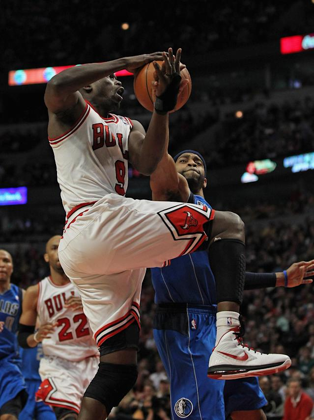 CHICAGO, IL - APRIL 21: Loul Deng #9 of the Chicago Bulls is fouled while shooting by Vince Carter #25 of the Dallas Mavericks at the United Center on April 21, 2012 in Chicago, Illinois. The Bulls defeated the Mavericks 93-83. NOTE TO USER: User expressly acknowledges and agress that, by downloading and/or using this photograph, User is consenting to the terms and conditions of the Getty Images License Agreement. (Photo by Jonathan Daniel/Getty Images)