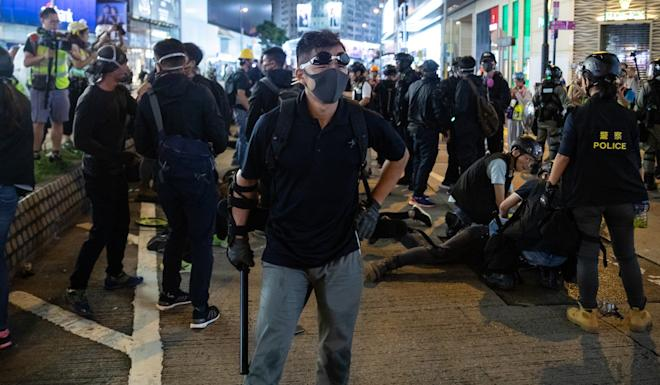 Men believed to be police officers dressed as protesters detain demonstrators on Hennessy Road. Photo: Kyle Lam/Bloomberg