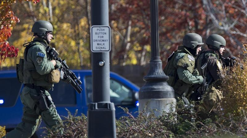 Police and swat team members respond to a call of a shooting at the Azana Spa in Brookfield, Wis. Sunday , Oct. 21, 2012. Multiple people were wounded when someone opened fire at the spa near the Brookfield Square Mall. Deputies are still looking for the gunman. (AP Photo/Tom Lynn)