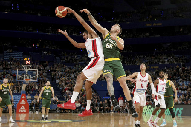 Canada's Thomas Scrubb, left, and Mitch Creek, of Australia, jump for the ball during their exhibition basketball game in Perth, Australia, Friday, Aug. 16, 2019. (Richard Wainwright/AAP Image via AP)