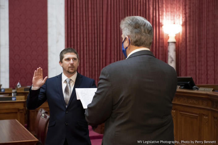 West Virginia House of Delegates member Derrick Evans, left, is given the oath of office Dec. 14, 2020, in the House chamber at the state Capitol in Charleston, W.Va. Evans, a West Virginia state lawmaker resigned Saturday, Jan. 9, 2021 as he faces charges of entering a restricted area of the U.S. Capitol after he livestreamed himself with rioters. (Perry Bennett/West Virginia Legislature via AP)