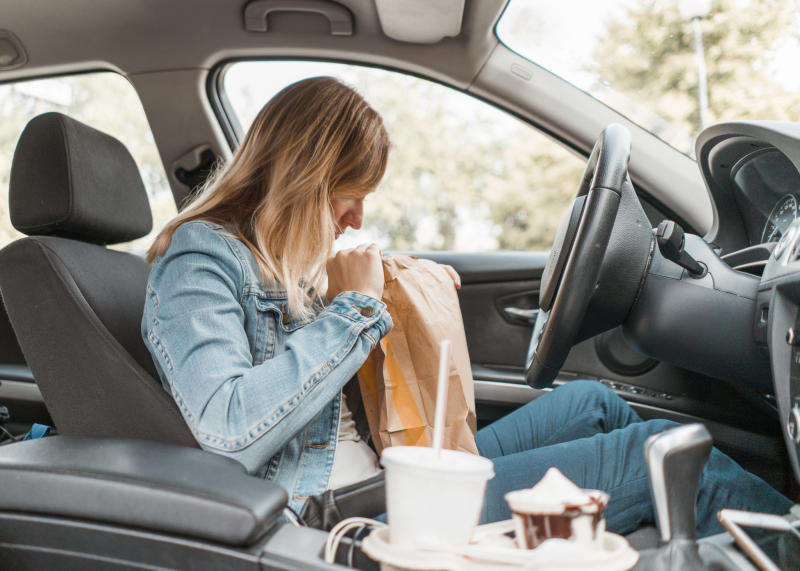 Young woman sitting in her car opens a McDonald's bag.