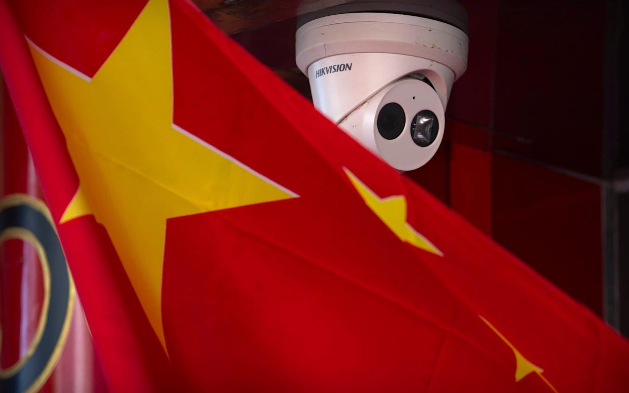 A Chinese flag hangs near a Hikvision security camera outside of a shop in Beijing - AP