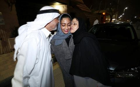 Hannan Iskandar is kissed by her parents, after she drove her car in her neighborhood, in Al Khobar - Credit: Reuters