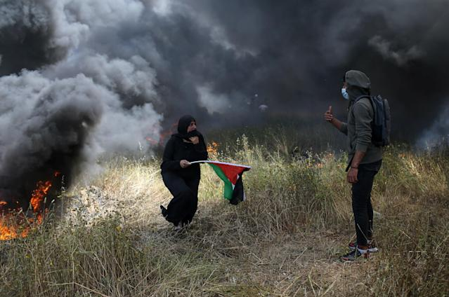 <p>A woman holds a Palestinian flag during clashes with Israeli troops at the Israel-Gaza border at a protest demanding the right to return to their homeland, in the southern Gaza Strip, April 6, 2018. (Photo: Ibraheem Abu Mustafa/Reuters) </p>