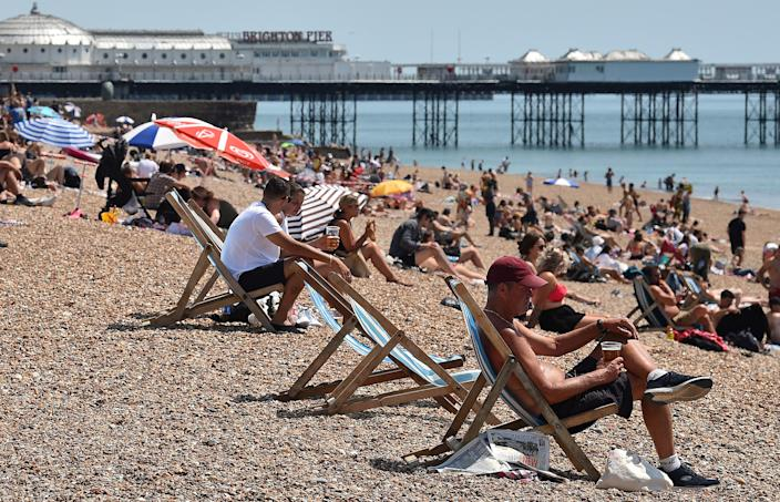 People sit in deckchairs as they enjoy the sunshine on the beach near the Brighton Pier (Picture: Getty)