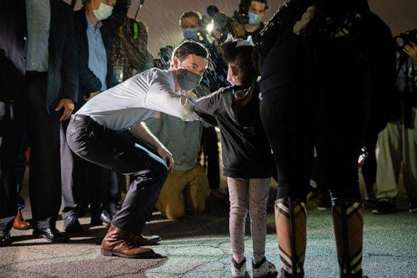 PHOTO: Democratic Senate candidate Jon Ossoff bumps elbows with a young supporter at a campaign event on Nov. 10, 2020, in Atlanta. (Elijah Nouvelage/Getty Images)