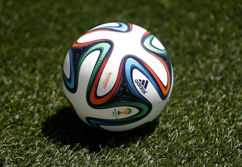 FILE - In this May 31, 2014, file photo an official 2014 FIFA World Cup soccer ball lies on the grass during an open practice by the United States in Harrison, N.J. A study, from the University of Glasgow and reported Monday, Oct. 21, 2019, in New England Journal of Medicine, of former professional soccer players in Scotland found that they were less likely to die of common causes such as heart disease and cancer compared with the general population but more likely to die from dementia. (AP Photo/Julio Cortez, File)