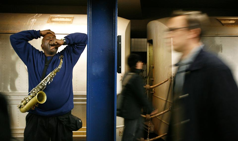 Musician Lew Jordan yawns while taking a break from playing the saxophone for train riders in the subway system of New York April 13, 2007. REUTERS/Lucas Jackson (UNITED STATES)