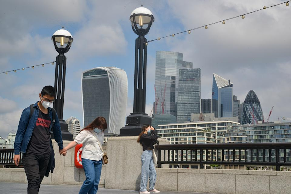 People walk next to the Thames with London's financial district in the background
