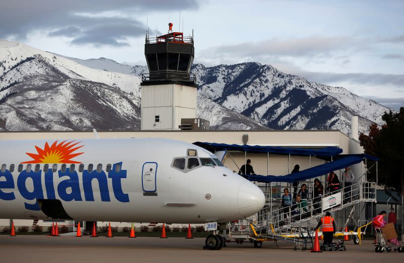 FILE PHOTO: Airline passengers walk next to an Allegiant Air commercial flight near an air traffic control tower operated by Serco nc. at the Ogden-Hinckley Airport in Ogden
