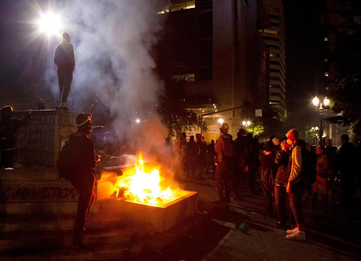 FILE - In this July 4, 2020, file photo, protesters gather near a fire in downtown Portland, Ore. Oregon's largest city is in crisis as violent protests have wracked downtown for weeks.